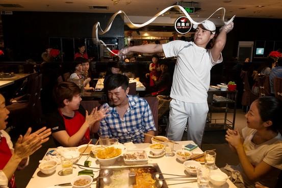 "Gilles Sabrie for Wall Street Journal一名海底捞员工(右)在北京一家分店的餐桌前表演""捞面舞""。"