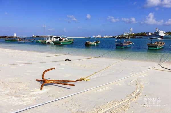 永兴岛美丽的白色沙滩,渔船静静漂浮在清澈透明的水中,岸边的沙子洁白细腻。