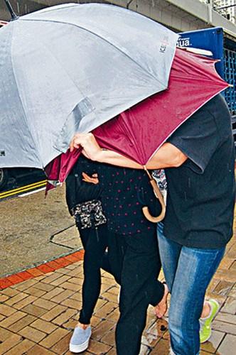 报假案老妇右二由女儿撑伞掩面离开法庭。香港星岛日报图