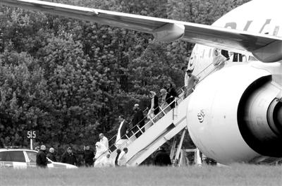"""5月24日,英国伦敦斯坦斯特德机场,乘客正从被""""拦截""""客机上下来。"""