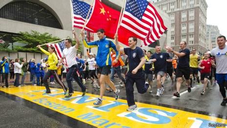 选手们在跑步时高举三面美国国旗和一面中国国旗,悼念死者。