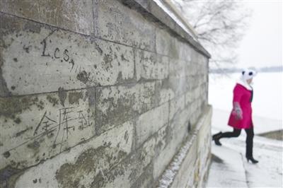 """""""天坛签名墙"""" 今年新京报曾报道,北京多处文物古迹遭涂鸦,天坛回音壁变成签名墙。图为2月25日,颐和园一砖墙上被刻的游客名字。新京报记者 浦峰 摄"""