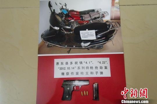 """被警方缴获作案摩托车辆、仿""""六四""""手枪1支、子弹3发。 严初 摄"""