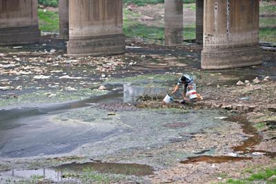 5月27日,一位村民正被严重污染的南沙河河道里打水准备浇菜,其下游不远处,即是沙河水库。新京报记者周岗峰 摄