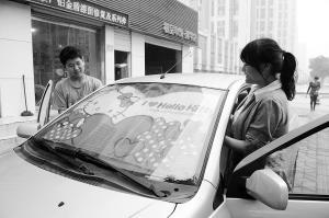 女车主选用了卡通造型的汽车遮阳帘,既活泼又防晒,为车主带来轻松心情。 记者 张晓峰 摄
