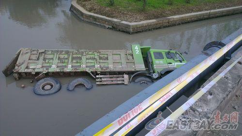 一辆垃圾清运车在路口连撞三车,坠入河道中。