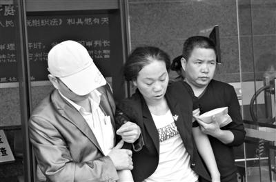 5月30日,项生源妻子虞水华在宣判后晕倒,闭庭后被家人搀扶着走出法院。新京报记者 刘一丁 摄