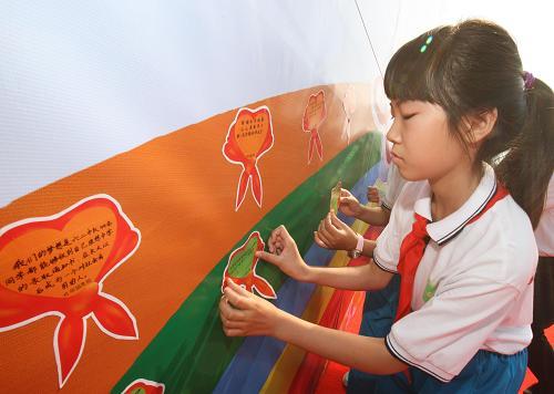 """5月31日,学生们在张帖写有愿望的""""红领巾梦想卡""""。新华社记者 赖向东 摄"""