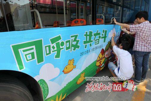 """石家庄环保志愿者给公交车""""穿上""""环保衣(图)"""
