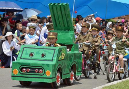 在儿童节庆祝活动上,一名朝鲜儿童穿着军装、开着载有火箭发射装置模型的玩具车。