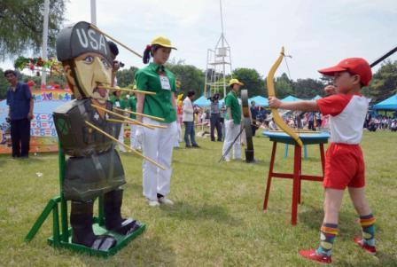 在儿童节庆祝活动上,一名朝鲜儿童朝着一个美兵形象靶子射箭。