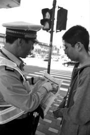 今天上午,在周家嘴路黄兴路路口,执勤民警对闯红灯的行人进行教育 晚报记者 周斌 现场图片