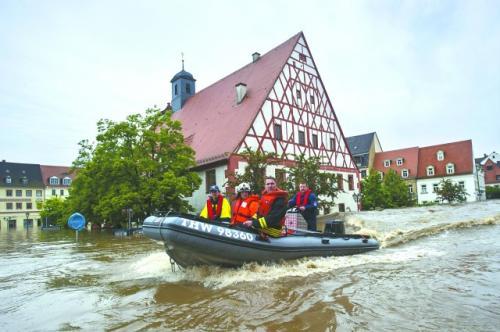 6 月3 日,在遭遇严重洪灾的德国东部城市格里马,救援人员使用救生筏帮助居民转移。