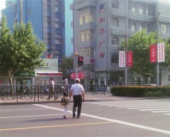中国/加华广场门口,由于不愿长时间等待,老爷爷拉着孩子闯红灯。