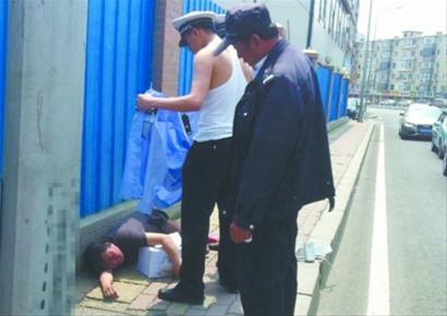 昨日,在大连市沙河口区中山路与连山街路口,一位中年妇女晕倒在路边,一名交警脱下警服为其遮阳。微博截图