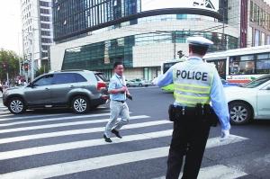 昨日,上海南京西路华山路路口,当值交警正在劝导一名闯红灯的市民。早报记者 杨一 图
