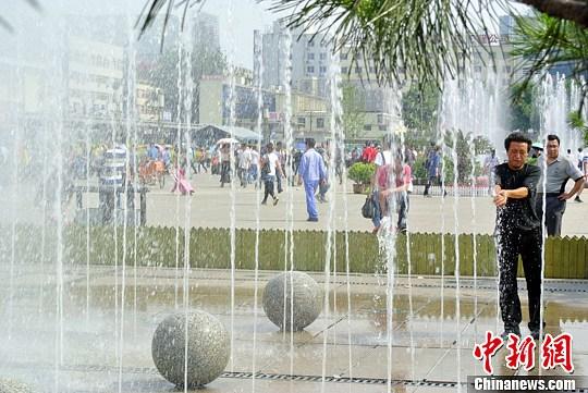 6月4日,山西太原火车站,候车的农民工戏水乘凉。当日山西各地迎来高温天气,局部地区达到35℃。中新社发 韦亮 摄