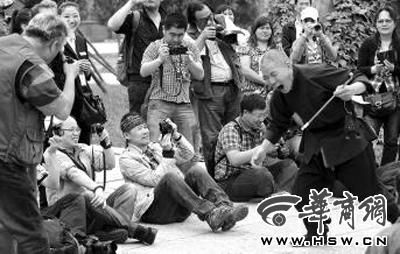 在西岳庙,王石席地而坐拍摄华阴老腔表演