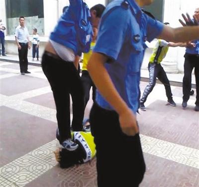 """""""延安城管暴力执法""""视频中,刘国峰被一名城管队员跳起来踩中头部,致其昏迷。视频截图"""