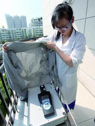 实验人员将格子衬衣打开遮挡光度计的传感器