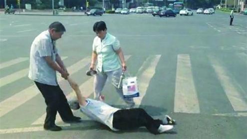 中年男子粗暴地把倒在地上的老人拖到路边,老人的鞋子都被拖掉了