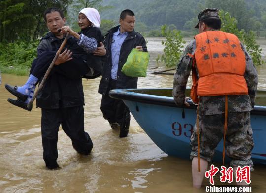 图为,安徽东至部分农村受到暴雨影响,部分农村出现险情,当地公安、消防等部门紧急转移被困群众。 王玮 摄