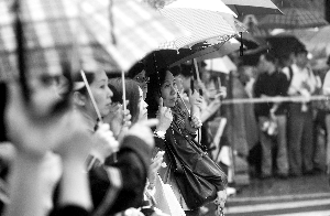 昨天,在东直门中学考点门外,雨中等待孩子出考场的家长翘首以盼。晨报记者 李木易/摄