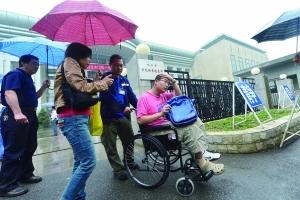 昨天在东直门中学考点,考务人员用轮椅推着一名骨折考生入场。晨报记者 李木易/摄