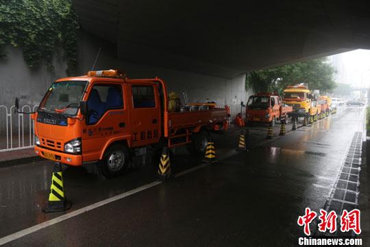 """图为2012年""""北京721水灾""""市区积水重点路段广渠门桥下,北京排水集团新购置的大型移动泵车""""龙吸水""""多日来在此待命,保障桥区交通。中新社发 杨可佳 摄"""