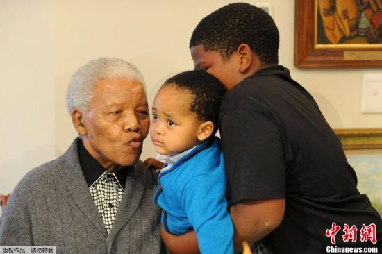 当地时间2012年7月18日,南非东开普省,前南非总统曼德拉在家中和家人庆祝自己的94岁生日。图为曼德拉亲吻自己的重孙。