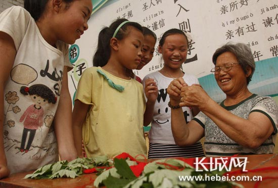 袁庄小学学生在老师的指导下学习缝制香包。陈志付/摄。