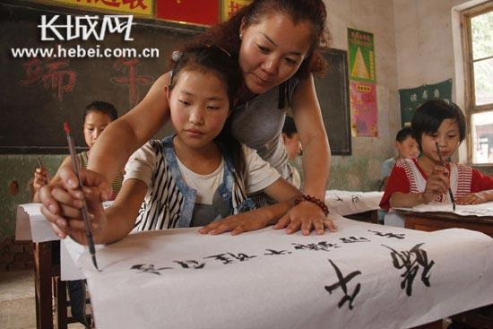袁庄小学学生在老师的指导下书写端午诗词。陈志付/摄。