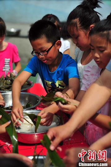 6月9日,沈阳市铁路第三小学的学生包粽子庆祝端午节的到来。中新社发 于海洋 摄