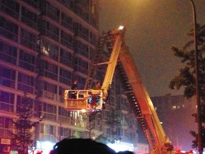 消防队员架起云梯将两被困住户救下。小好 摄