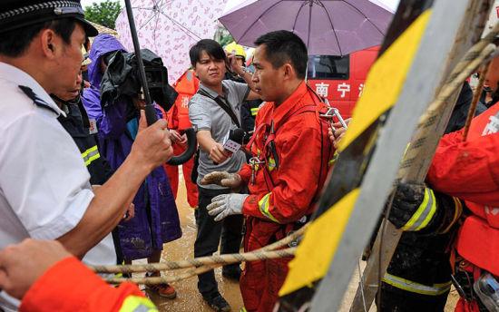 图为一名刚下井搜寻的消防官兵向地面人员介绍情况(图片来源:中新网)