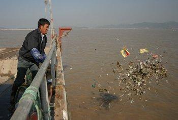 图为乐清游船渔民向大海倾倒垃圾的情景。