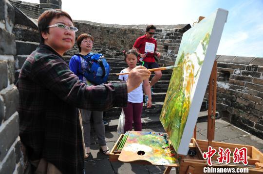 """艺术家现场创作20米长油画""""长城""""。 张帆 摄"""