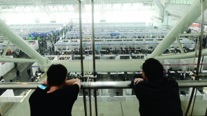 5月19日,两个求职者在国展中心二楼,望着楼下的求职大军 (资料图片)