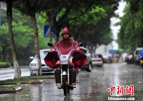 6月15日,海口市民冒雨出行,受今年首个热带低压影响,海南大部出现明显降雨天气。中新社发 骆云飞 摄