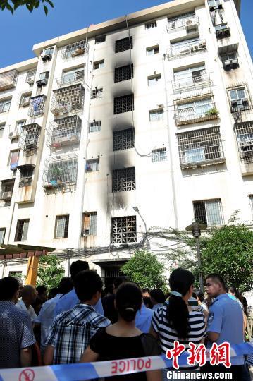 图为发生火宅的居民楼前站着许多民众。 刘占昆 摄