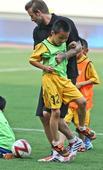 图文:小贝与南京小学生踢球 欢声笑语