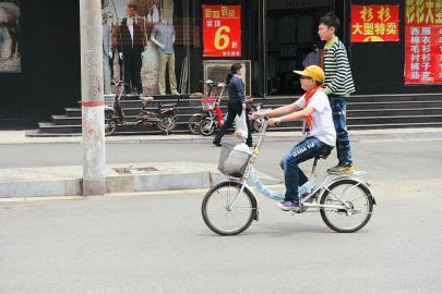 """骑自行车上学的孩子在路上玩起了""""杂技""""图片"""