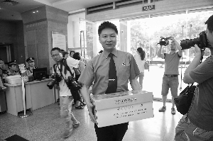 昨日,重庆市检方拿着证据袋进入法院。新华社发