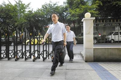 昨日19时,赵红霞代理律师张智勇(左一)在法院门外的小店吃了一碗米粉后,匆匆走回法院。赵亢 摄