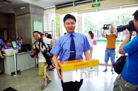 6月20日,重庆市检方拿着证据袋进入法院。 新华社发