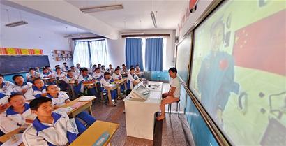 青岛实验初级中学的学生兴趣盎然地收看太空授课