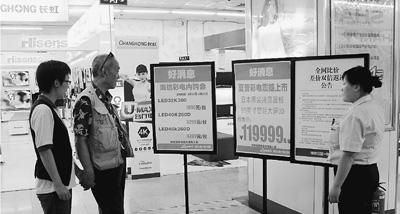 节能补贴政策结束后,家电卖场通过多种促销活动吸引消费者。图为近日顾客在北京市海淀区某家电卖场内查看促销海报详情。严 瑜摄