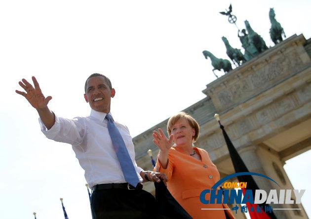 美国总统奥巴马(左)和德国总理默克尔在柏林勃兰登堡门前向民众挥手示意。