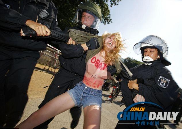 """示威者上身赤裸、仅穿着牛仔短裤,并在胸部和腹部写上醒目的红色标语""""奥巴马,帮帮我们""""。"""