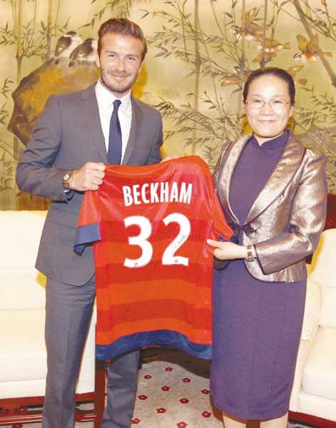 贝克汉姆(左)向上海市副市长赵雯赠送签名球衣。